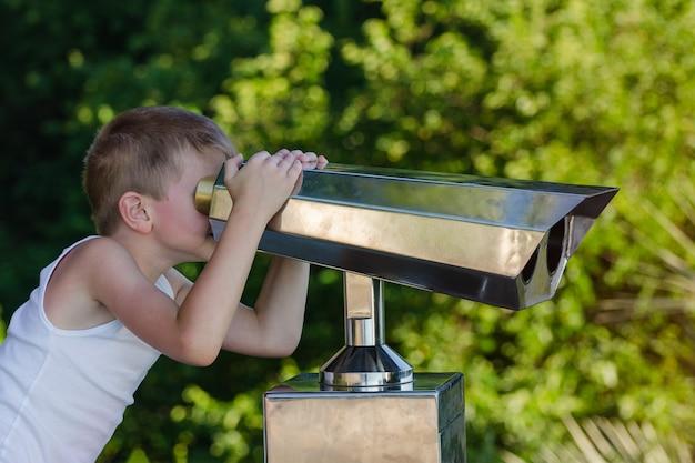 Boy looks through telescope at city sights.