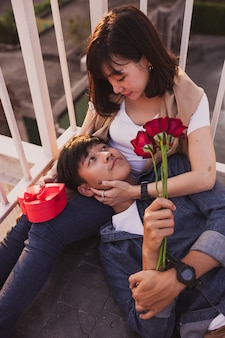 Boy lying on his girlfriend's legs with roses in his hand