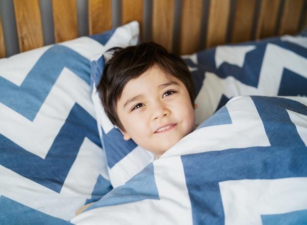 Мальчик лежал в постели расслабляясь утром