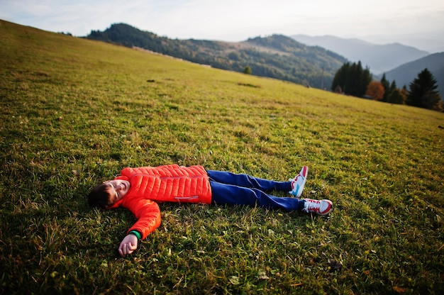地平線にゴージャスな山脈と草の中に横たわっている少年。