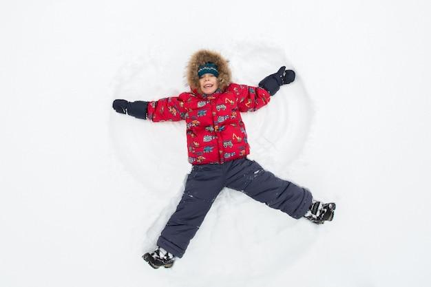 Мальчик лежит в снегу, делая снежного ангела