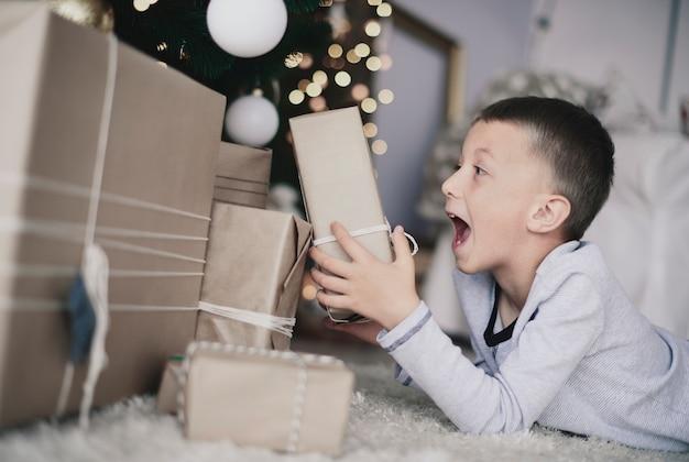 正面に横たわって贈り物を見ている少年
