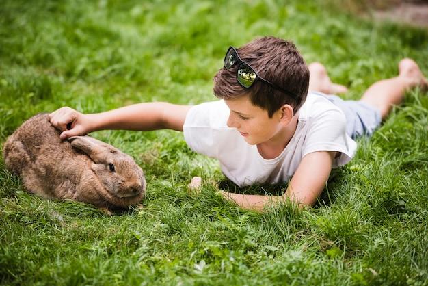 彼のウサギを愛する緑の草の上に横たわっている少年