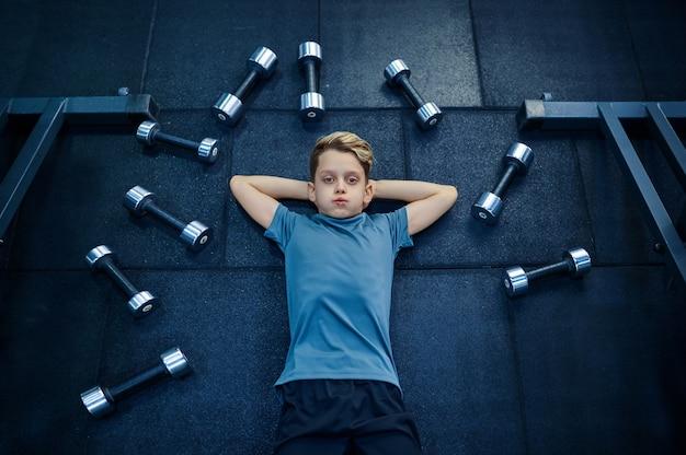 체육관에서 많은 아령 중 매트에 누워 소년. 스포츠 클럽, 건강 관리 및 건강한 라이프 스타일 훈련, 운동 모범생, 낚시를 좋아하는 청소년