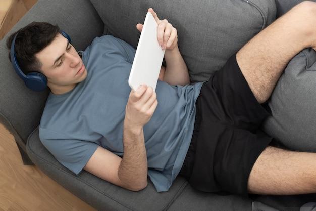 Мальчик лежит на диване с наушниками и планшетом мальчик на диване, вид сверху мальчик на диване с планшетом