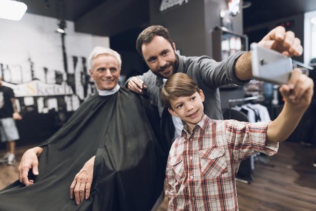 Boy make selfie with barber in barbershop