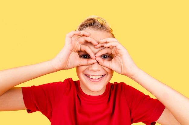 Boy making binocular with hands on his eyes