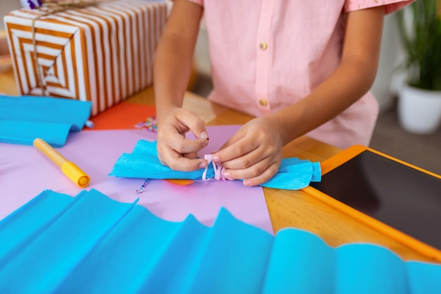 Boy making bow. close up of schoolboy wearing pink shirt preparing paper bow for present box
