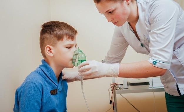 Boy making inhalation with nebulizer at clinic.