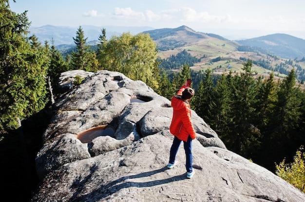 自撮りをする少年。山で美しい日にハイキングをしたり、岩の上で休んだり、山頂の素晴らしい景色を眺めたりする子供たち。子供とのアクティブな家族の休暇の余暇。屋外の楽しさと健康的な活動。