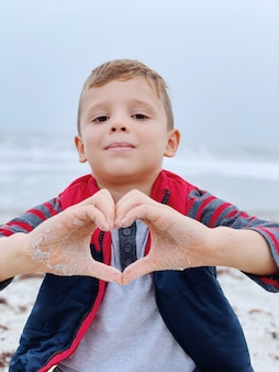 Boy making shape of heart with hands for valentine's day on the beach.