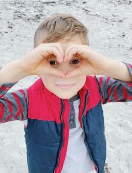 Мальчик делает форму сердца руками на день святого валентина.