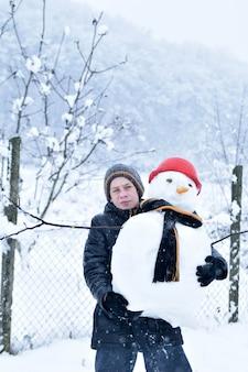 Boy making a snowman, fun winter activities