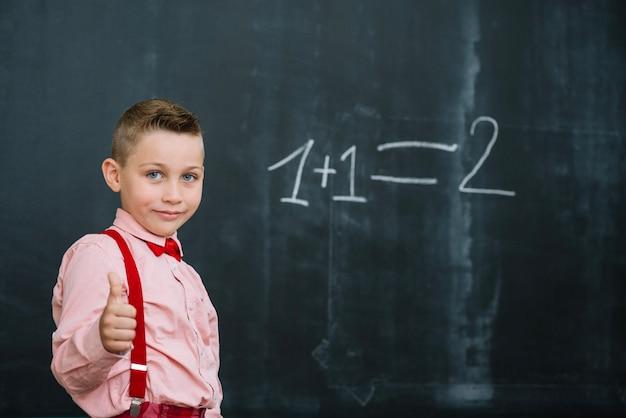 Boy at math lesson gesturing thumb up