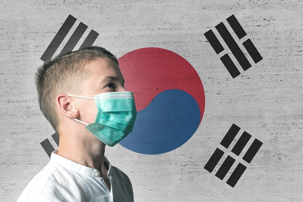 Boy in a medical mask on his face on background of south korea flag.