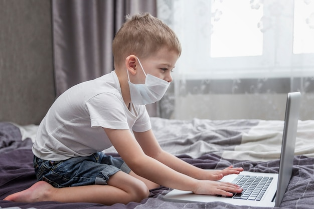 A boy in a medical mask sits in front of a laptop at home in bed. distance learning. quarantine in the context of a coronavirus pandemic.