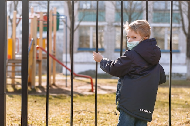 A boy in a medical mask stands next to a metal fence. a child yearns for playing on the playground during quarantine