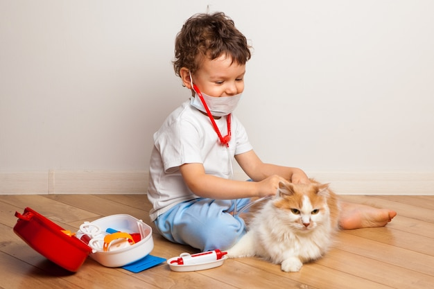 A boy in a medical mask with a stethoscope plays with a disgruntled cat in the hospital.
