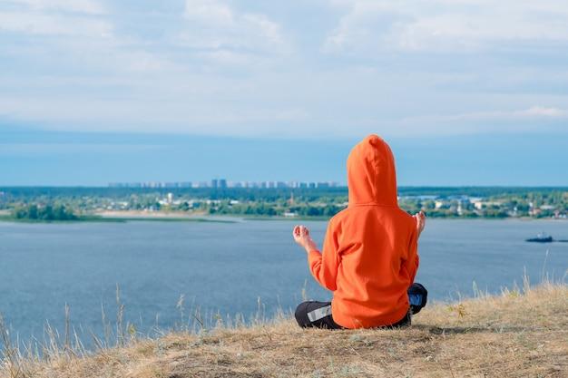 Мальчик медитирует на склоне холма на фоне морского пейзажа с медитацией