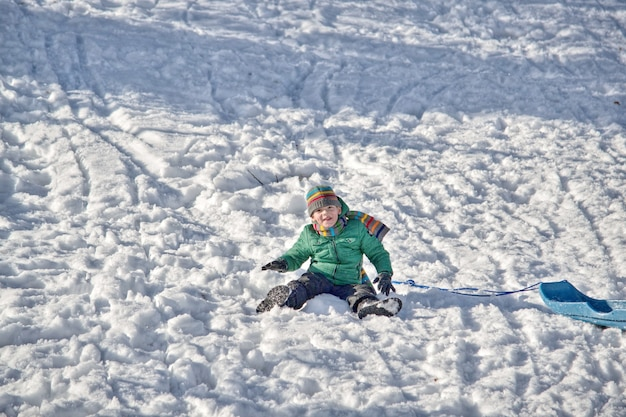 Boy in the mountains rides in the snow on a sled Premium Photo