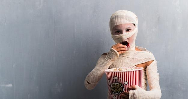 Boy in mummy costume eating popcorns for halloween holidays