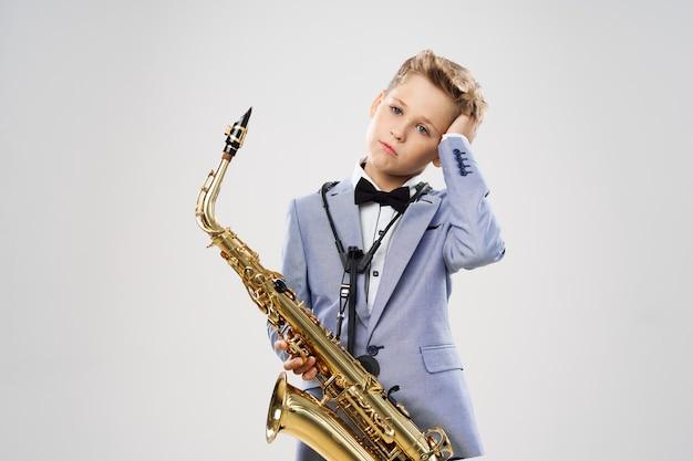 Мальчик-музыкант в костюме играет на саксофоне