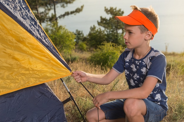 Boy in nature, in the forest sets up a tent and equips a bivouac, in the background a lake or a sea, a summer hiking trip, a camping