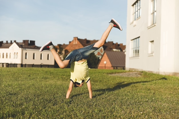 Boy in nature is engaged in acrobatics.