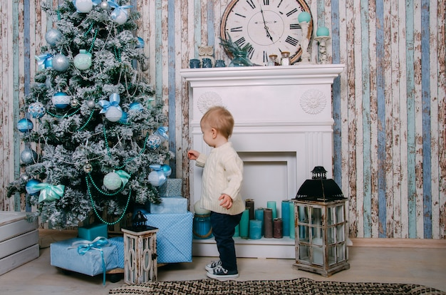 Boy near the fireplace and christmas tree