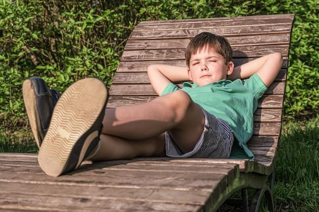 Tshirt와 반바지에 8 년의 소년은 녹색 잎의 배경에 대해 태양에 나무 갑판 의자에 놓여 있습니다. 편안하고 게으른 자세의 소년