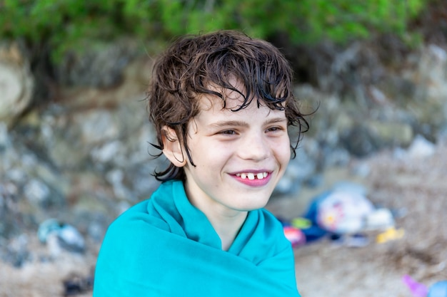10살짜리 소년이 바다에서 수영한 후 수건에 싸여 있습니다. 프랑스의 휴일.