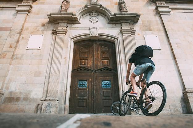 木製のドアの前で自転車に乗る少年コピースペーススポーツ都市サイクリングライフスタイルの概念