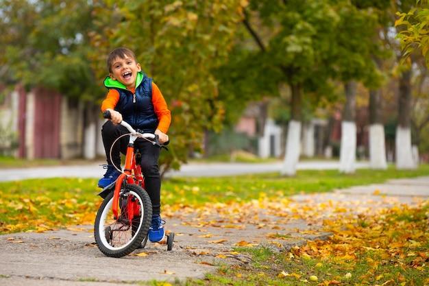 秋の公園で自転車に乗る少年。幸せな笑顔の子供が屋外でサイクリング。アクティブなライフスタイル、趣味。サイドスペースが空の写真。