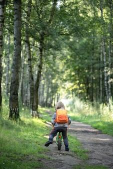 Мальчик на беговом велосипеде катается по лесной тропинке летом