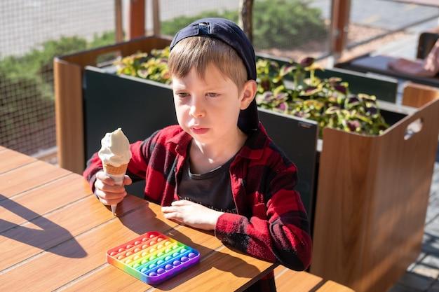晴れた日の少年はアイスクリームを食べて遊んでいます。トレンディな新しいおもちゃ。子供のための平和な娯楽