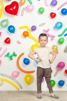 Мальчик на белом фоне с разноцветными воздушными шарами мальчик в майке и штанах