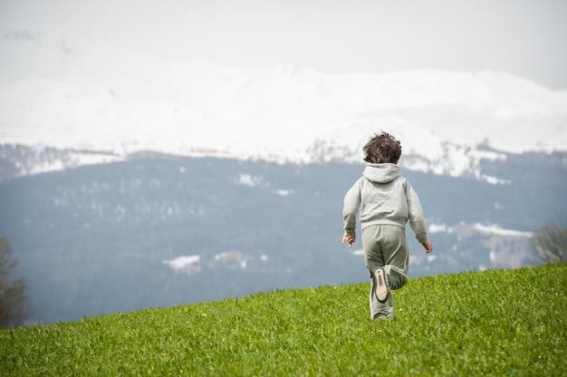 美しい山の草原の少年