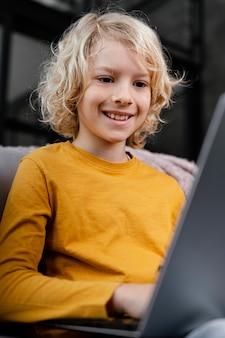Мальчик на диване с ноутбуком