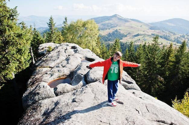 山の頂上にいる少年。山で美しい日にハイキングをしたり、岩の上で休んだり、素晴らしい景色の頂上を眺めたりする子供たち。子供とのアクティブな家族の休暇の余暇。屋外の楽しさと健康的な活動。