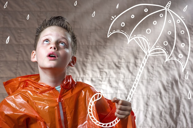 Boy in an orange raincoat and with a painted umbrella stands in the rain