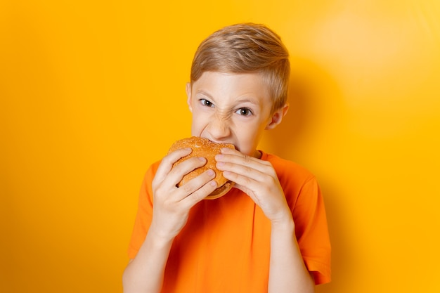 A boy in an orange t-shirt holds a hamburger in both hands and greedily bites it on a yellow background