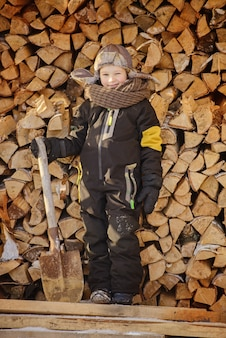 A boy in overalls, a hat with earflaps and a shovel stands near the firewood