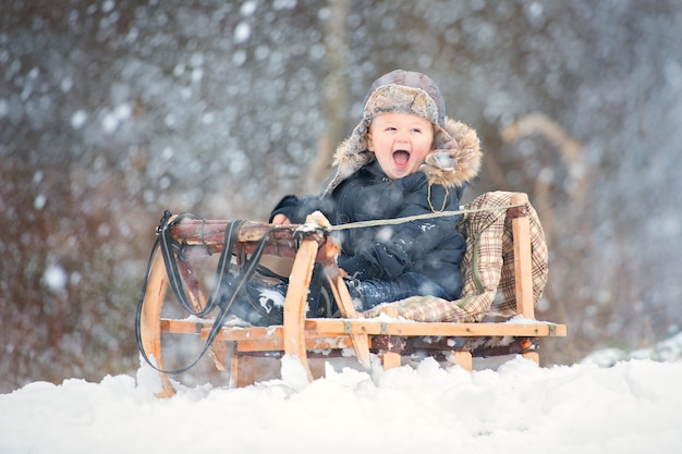 A boy in an overalls with fur and a hat with earflaps sits in a wooden sled.