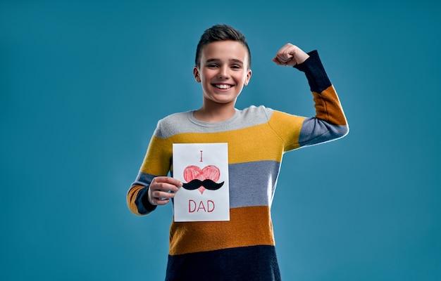 소년 파란색에 고립 된 선물로 그의 아버지를위한 카드를 그렸습니다.