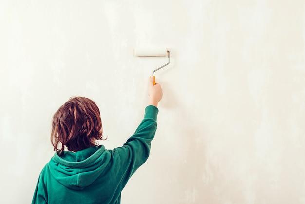 Мальчик красит стену