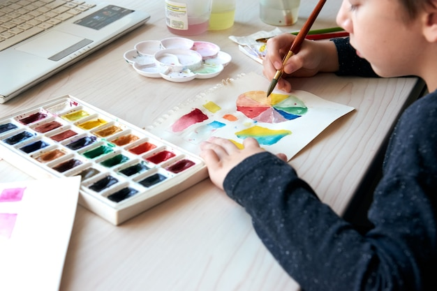 Boy painting pictures with watercolor paints during art lesson online