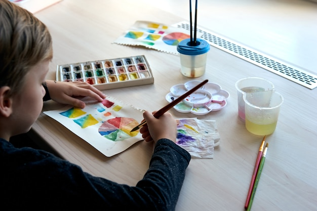 Boy painting pictures with watercolor paints during art lesson. pupil on drawing with brush. watercolor color wheel and palette. color theory beginner hobby lessons.