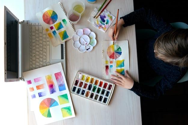 アートレッスン中に水彩絵の具で絵を描く少年。ブラシで描く瞳孔。水彩カラーホイールとパレット。色彩理論初心者の趣味のレッスン。