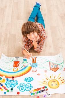 Рисование мальчика. молодой мальчик расслабляется во время рисования акварелью, лежа на полу