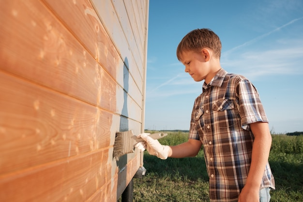 Boy paints the wall of a wooden house. son helps parents with painting the garden house